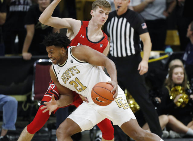 Colorado forward Evan Battey, front, drives to the basket as Utah center Branden Carlson defends in the first half of an NCAA college basketball game Sunday, Jan. 12, 2020, in Boulder, Colo. (AP Photo/David Zalubowski)