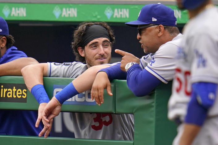 Los Angeles Dodgers manager Dave Roberts, right, talks with Cody Bellinger, left, in the dugout during a baseball game against the Pittsburgh Pirates in Pittsburgh, Thursday, June 10, 2021. (AP Photo/Gene J. Puskar)