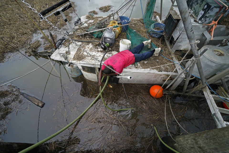 John Williams, a marina employee, tries to help raise a shrimp trawler that sunk during Hurricane Ida, in the aftermath of the storm in Plaquemines Parish, La., Monday, Sept. 13, 2021. (AP Photo/Gerald Herbert)