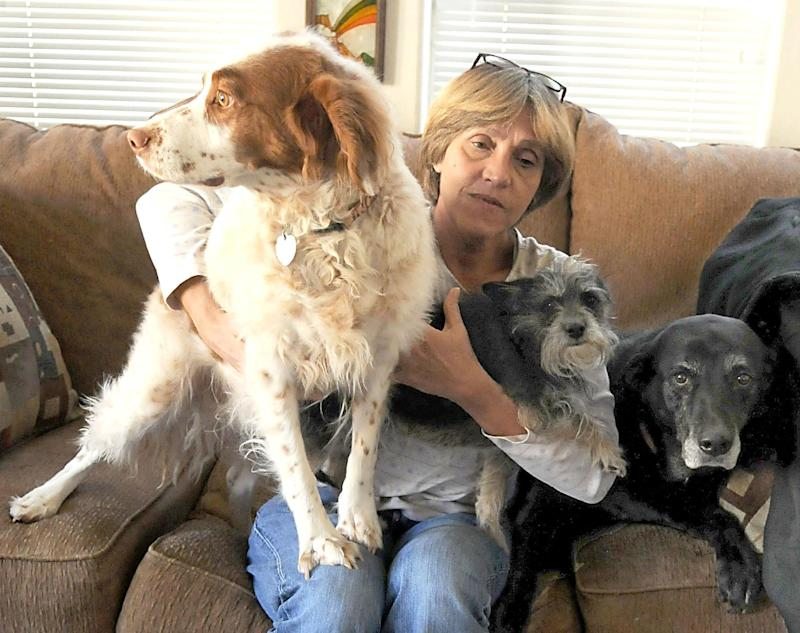 In this photo taken Dec. 1, 2011, Lynn Jones sits with her three dogs, from left, Junior, Manny and Jewel, at her Lockwood, Nev. home. Jones, a former airport baggage handler, was fired after refusing to load an ailing dog onto a plane at Reno-Tahoe International Airport. (AP Photo/The Reno Gazette-Journal, Marilyn Newton)  NEVADA APPEAL OUT;  NO SALES