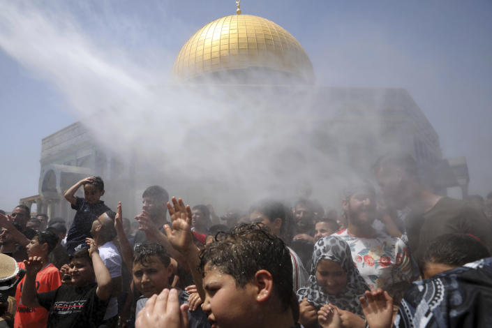 Muslim worshippers are sprayed with cool water during Friday prayers for the Muslim holy month of Ramadan at the Dome of the Rock Mosque in the Al Aqsa Mosque compound in the Old City of Jerusalem, Friday, April 30, 2021. (AP Photo/Mahmoud Illean)