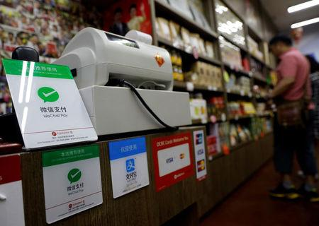Signs accepting WeChat Pay and AliPay are displayed at a shop in Singapore