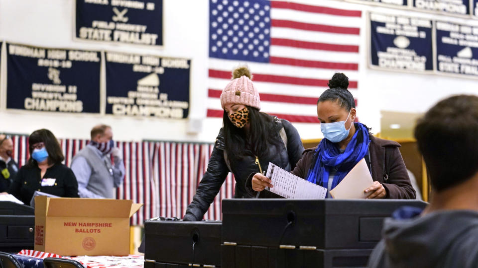 FILE— In this Nov. 3, 2020 file photograph, two women, wearing protective masks due to the COVID-19 virus outbreak, cast their ballots at a polling station at Windham, N.H. High School. Auditors have found no evidence of fraud or political bias in a controversial election in Windham, N.H. (AP Photo/Charles Krupa, File)