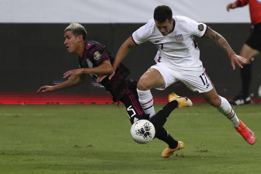 Mexico's Uriel Antuna, left, and United States' Aaron Herrera fight for the ball during a Concacaf Men's Olympic Qualifying championship soccer match in Guadalajara, Mexico, Wednesday, March 24, 2021. (AP Photo/Fernando Llano)