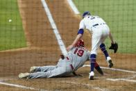Los Angeles Angels' Juan Lagares (19) scores on a wild pitch by Texas Rangers relief pitcher Kolby Allard, right, who was unable to handle the high throw to the plate on the scoring play in the third inning of a baseball game in Arlington, Texas, Wednesday, Aug. 4, 2021. (AP Photo/Tony Gutierrez)