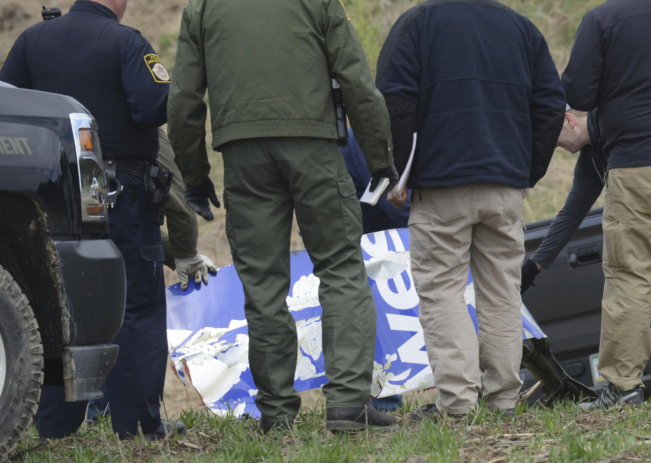 <p>National Transportation Safety Board investigators examine a piece of debris from the plane that made an emergency landing Tuesday after a fatal engine mishap in Penn Township, Berks County, Pa. field Wednesday, April 18, 2018, on state game lands. (Photo: Bill Uhrich/Reading Eagle via AP) </p>