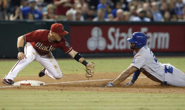 Arizona Diamondbacks' Cliff Pennington, left, waits to tag out Los Angeles Dodgers' Matt Kemp as Kemp slides into third base trying to stretch a double into a triple during the third inning of a baseball game Wednesday, Aug. 27, 2014, in Phoenix. Kemp knocked in two runs on his double. (AP Photo/Ross D. Franklin)
