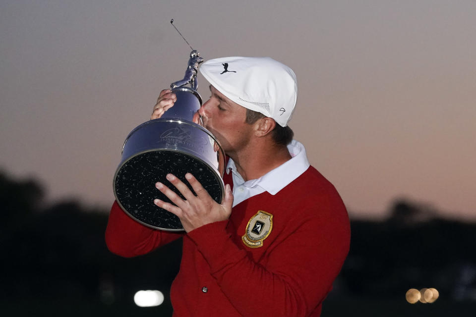 Bryson DeChambeau kisses the championship trophy after he won the Arnold Palmer Invitational golf tournament Sunday, March 7, 2021, in Orlando, Fla. (AP Photo/John Raoux)