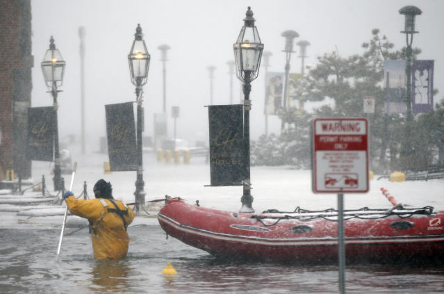 <p>A Boston firefighter wades through flood waters from Boston Harbor on Long Wharf in Boston, Thursday, Jan. 4, 2018. (Photo: Michael Dwyer/AP) </p>