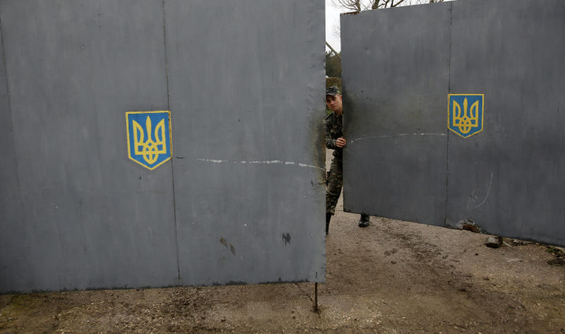 A Ukrainian soldier closes a gate as he and others guard a military base at the Black Sea port of Sevastopol in Crimea, Ukraine, Saturday, March 8, 2014. A Ukrainian officer at the military base said that pro-Russia soldiers crashed a truck through its gates late on Friday in an attempt to take it over. (AP Photo/Darko Vojinovic)
