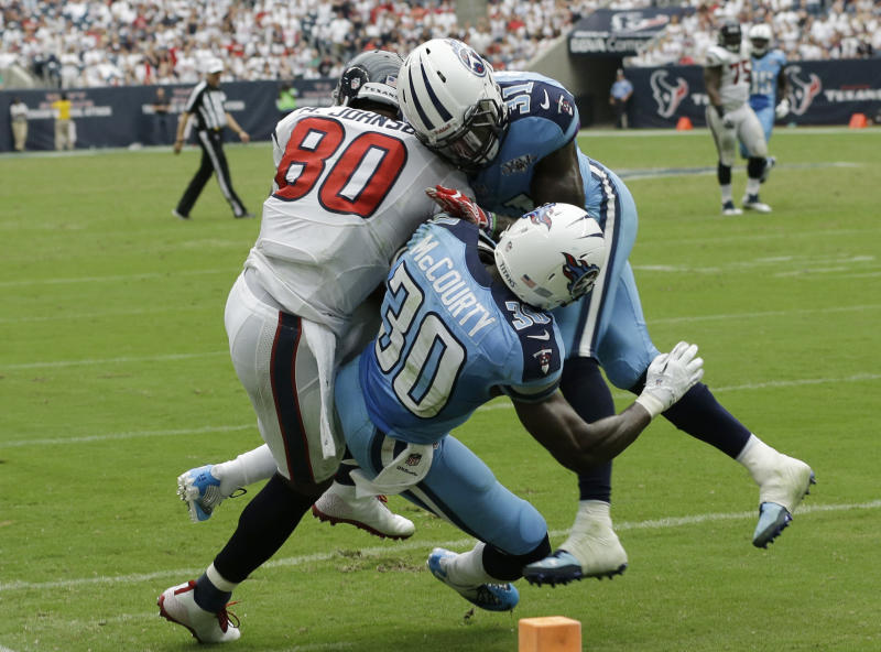 Houston Texans' Andre Johnson (80) is hit by Tennessee Titans' Bernard Pollard (31) and Jason McCourty (30) after a reception during the fourth quarter of an NFL football game Sunday, Sept. 15, 2013, in Houston. Johnson was injured on the play.  (AP Photo/David J. Phillip)