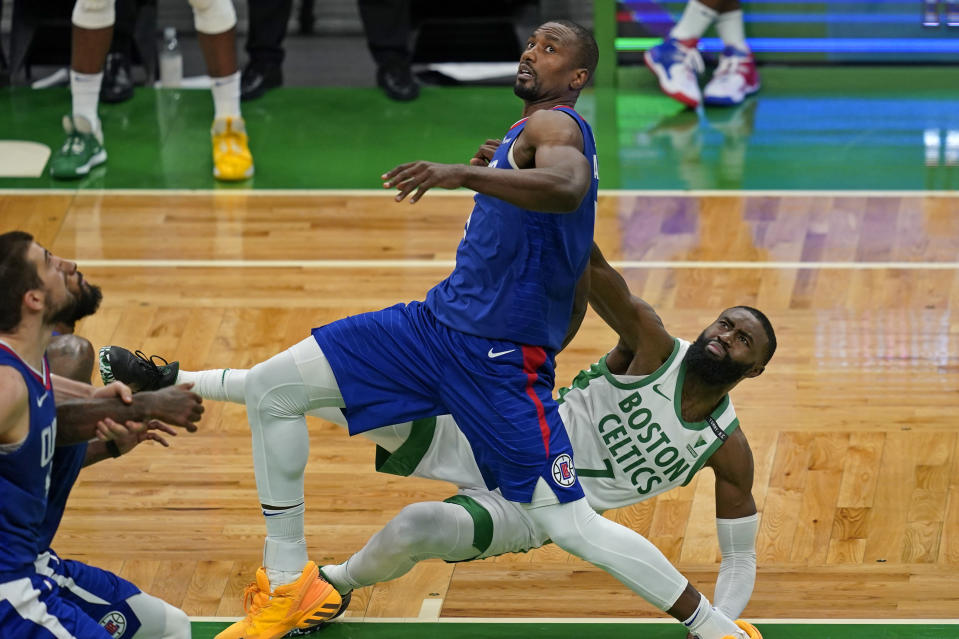 Boston Celtics guard Jaylen Brown (7) falls to the floor after struggling for rebound position with Los Angeles Clippers center Serge Ibaka in the fourth quarter of an NBA basketball game, Tuesday, March 2, 2021, in Boston. The Celtics won 117-112. (AP Photo/Elise Amendola)