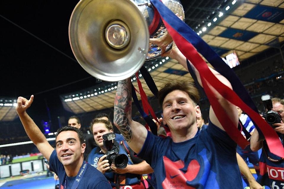 Barcelona's Lionel Messi celebrates with the trophy after their UEFA Champions League final match against Juventus, at the Olympic Stadium in Berlin, on June 6, 2015 (AFP Photo/Lluis Gene)