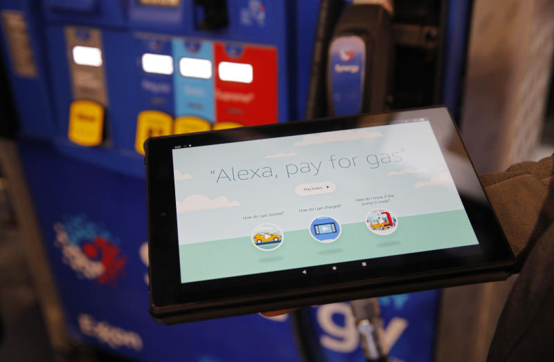An employee holds a tablet showing a video demonstrating the Alexa pay for gas feature in the Amazon booth at the CES tech show, Wednesday, Jan. 8, 2020, in Las Vegas. (AP Photo/John Locher)