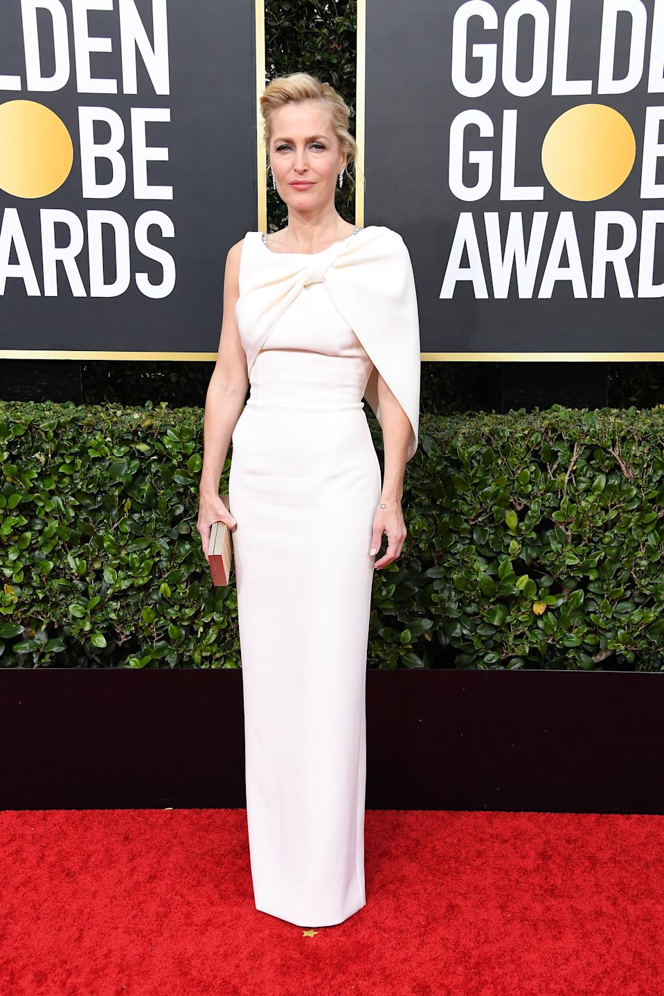 """Anderson arrived to celebrate her Netflix series """"The Crown"""" looking polished in a classic cream asymmetrical gown. (Photo by Steve Granitz/WireImage)"""