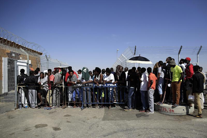African migrants enter the Holot detention center, southern Israel, Friday, April 11, 2014. Hundreds of African migrants gathered outside the Holot detention center in Israel's Negev desert on Friday to eat matzo and recall the Passover story - one of freedom from bondage - mere steps away from a detention facility where they are being held. (AP Photo/Tsafrir Abayov)