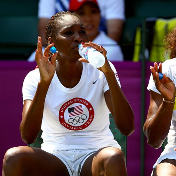 LONDON, ENGLAND - JULY 26: (L-R) Venus and Serena Williams of the United States wave while taking a break during the practice session ahead of the 2012 London Olympic Games at the All England Lawn Tennis and Croquet Club in Wimbledon on July 26, 2012 in London, England.  (Photo by Clive Brunskill/Getty Images)