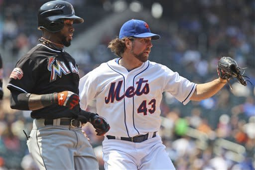 New York Mets starting pitcher R.A. Dickey, right, beats Miami Marlins' Jose Reyes to first base for an out during the eighth inning of the baseball game Thursday, Aug. 9, 2012 at Citi Field in New York. The Mets beat the Marlins 6-1. (AP Photo/Seth Wenig)