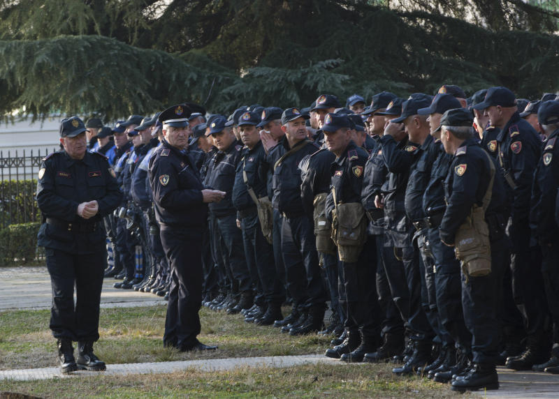 Policemen prepare to secure the Parliament building as opposition supporters gather to participate in an anti-government rally in capital Tirana, Albania, on Tuesday, Feb. 21, 2019. Albania's opposition supporters have surrounded the parliament building Thursday, asking for the resignation of the government which they allege is corrupt. (AP Photo/Visar Kryeziu)