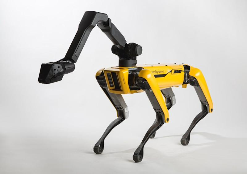 Mush! Watch a team of Boston Dynamics' SpotMini robot dogs pull a truck down the street
