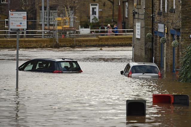 Cars are submerged as floodwater covers the roads and car parks in Mytholmroyd, West Yorkshire, after the River Calder burst its banks on Sunday. (Oli Scarff/AFP via Getty Images)