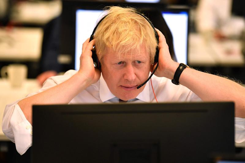 Britain's Prime Minister Boris Johnson speaks to a caller as he mans the phones at the Conservative Campaign Headquarters Call Centre (POOL/AFP via Getty Images)
