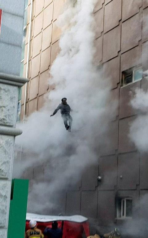 A survivor jumps down to an air mattress as he waits for rescue from a burning building in Jecheon - Credit: REUTERS