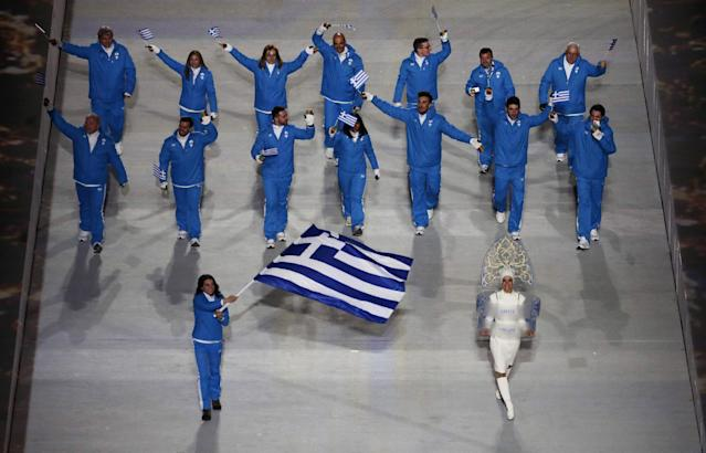 Panagiota Tsakiri of Greece holds her national flag and leads her team into the stadium during the opening ceremony of the 2014 Winter Olympics in Sochi, Russia, Friday, Feb. 7, 2014. (AP Photo/Charlie Riedel)