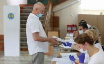 A man receives his ballot during a vote at a snap parliamentary election, in Chisinau