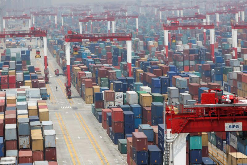 FILE PHOTO: A man walks in a shipping container area at Yangshan Port of Shanghai