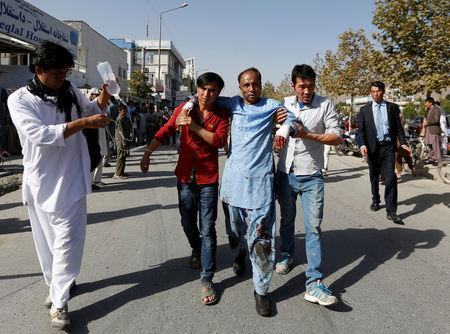Men help an injured man outside a hospital after a suicide attack in Kabul, Afghanistan July 23, 2016. REUTERS/Mohammad Ismail