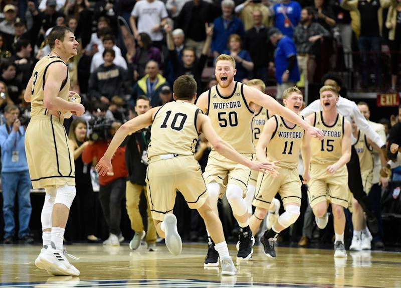 Wofford guard Fletcher Magee (3), guard Nathan Hoover (10), center Matthew Pegram (50), guard Ryan Larson (11) and guard Trevor Stumpe (15) celebrates their team's 70-58 win over UNC-Greensboro for the Southern Conference tournament championship, Monday, March 11, 2019, in Asheville, N.C. (AP Photo/Kathy Kmonicek)