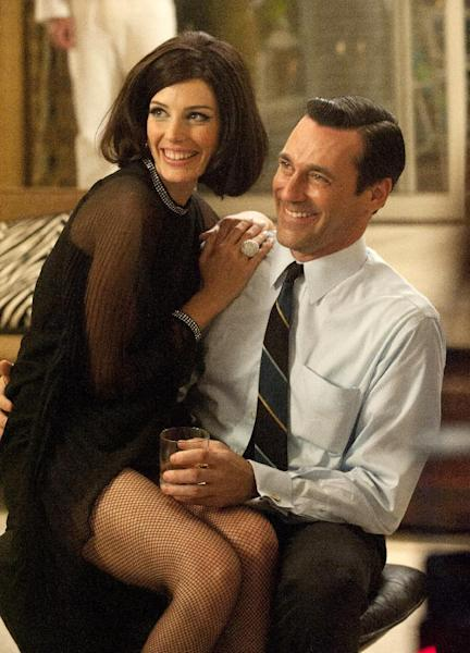 "This image released by AMC shows Jessica Pare as Megan Draper, left, and Jon Hamm as Don Draper in a scene from the season five premiere episode of ""Mad Men,"" where Megan surprises Don with a birthday party. On Thursday, July 19, 2012, the program received a total of 17 Emmy nominations including best actress in a drama series for Elisabeth Moss and best actor for Jon Hamm. The 64th annual Primetime Emmy Awards will be presented Sept. 23 at the Nokia Theatre in Los Angeles, hosted by Jimmy Kimmel and airing live on ABC. (AP Photo/AMC, Ron Jaffe)"