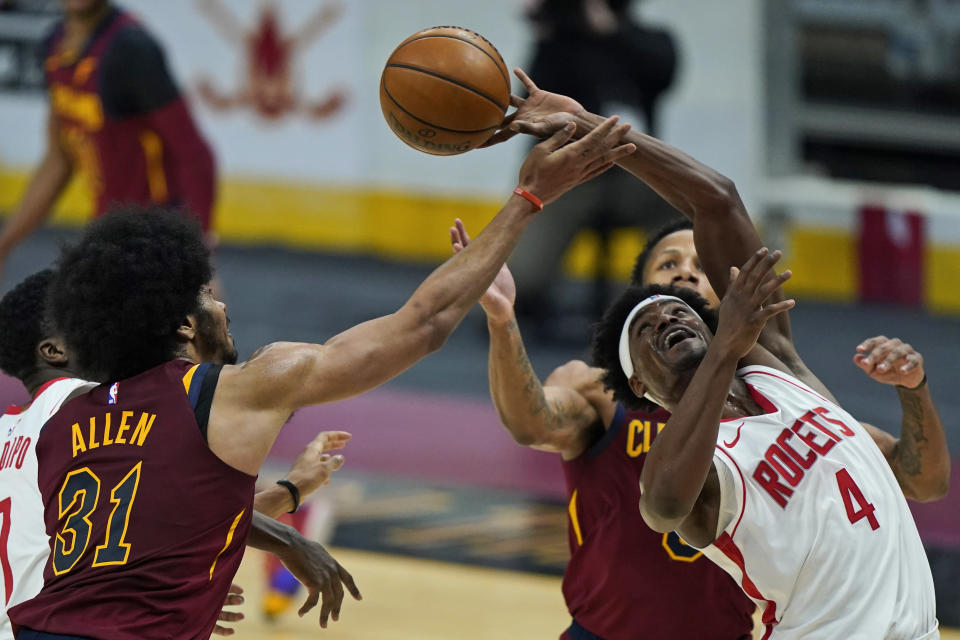 Houston Rockets' Danuel House Jr. (4) and Cleveland Cavaliers' Jarrett Allen (31) battle for a rebound in the first half of an NBA basketball game, Wednesday, Feb. 24, 2021, in Cleveland. (AP Photo/Tony Dejak)