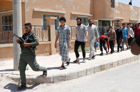 Islamic State prisoners, who were pardoned by a council that is expected to govern Raqqa once the group is dislodged from the Syrian city, walk behind a Kurdish policeman in Ain Issa village, north of Raqqa, Syria June 24, 2017. REUTERS/Goran Tomasevic