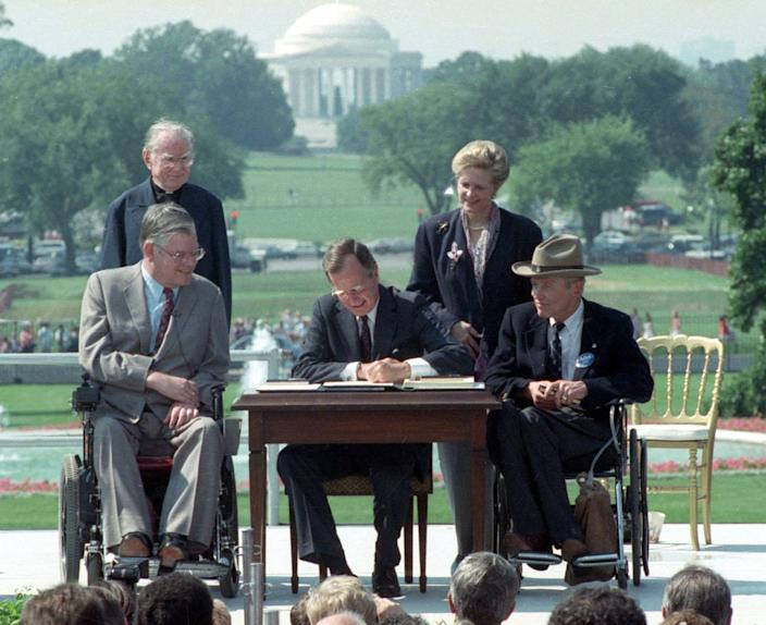 President George H. W. Bush signs the Americans with Disabilities Act at the White House on July 26, 1990, in Washington, D.C.