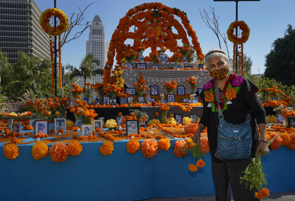 "Ofelia Esparza, 88, from East Los Angeles, brings fresh marigolds, often called ""flowers of the dead,"" for her annual Community Altar for the Day of the Dead, titled ""2020 Memorial to Our Resilience,"" at Grand Park in Los Angeles on Thursday, Oct. 29, 2020. (AP Photo/Damian Dovarganes)"