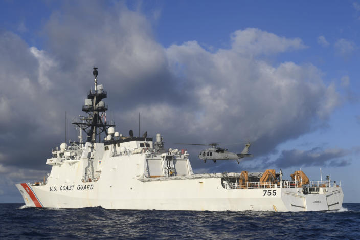 In this Aug. 25, 2020 photo provided by the U.S. Navy, an MH-60S Sea Hawk Helicopter hovers next to the the Legend-class cutter USCGC Munro in the Pacific Ocean. The Coast Guard cutter Munro had just embarked on a national security mission to patrol the maritime boarder between the United States and Russia in late June 2020, when one of its guardsman was diagnosed with COVID-19. Contract tracing led to more than a dozen other members of the ship's crew being ordered into quarantine for two weeks. (Mass Communication Specialist 3rd Class Madysson Anne Ritter/U.S. Navy via AP)