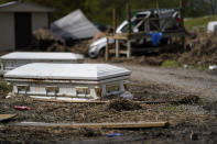 Displaced caskets that floated away from a cemetery during flooding sits along a road in Ironton, La., Monday, Sept. 27, 2021. A month after Hurricane Ida, small communities along Louisiana's southeastern coast are still without power or running water. Some residents have lost most of their possessions to the storm's floodwaters. (AP Photo/Gerald Herbert)
