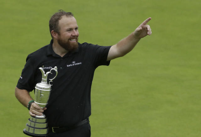 Ireland's Shane Lowry gestures to the crowd as he holds the Claret Jug trophy after winning the British Open Golf Championships at Royal Portrush in Northern Ireland, Sunday, July 21, 2019.(AP Photo/Matt Dunham)