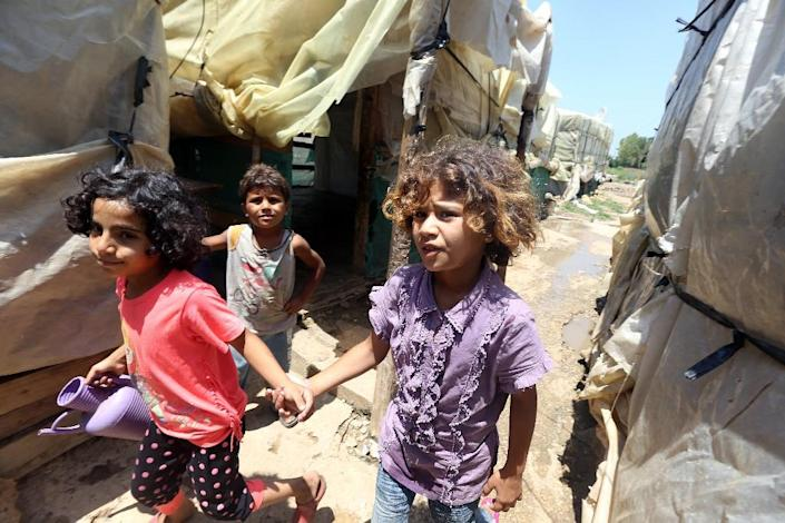 Syrian refugee children walk at an informal refugee camp in the area of Zahrani, south of the Lebanese capital Beirut, on July 9, 2015 (AFP Photo/Joseph Eid)