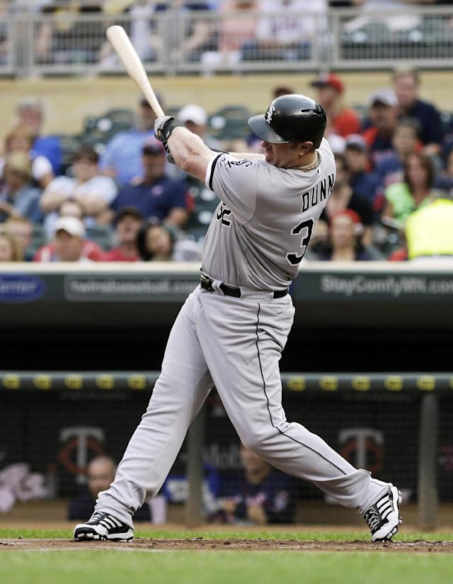 Chicago White Sox' Adam Dunn hits an RBI single off Minnesota Twins pitcher Mike Pelfrey top open scoring in the first inning of a baseball game, Thursday, Aug. 15, 2013 in Minneapolis. (AP Photo/Jim Mone)