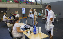 Gloria Raudjarv, 13-year-old girl, center, and her father Ivo, right, stand in front of a nurse to be registrateto for her first dose of the Covid-19 vaccine a vaccination center inside a sports hall in Estonia's second largest city, Tartu, 164 km. south-east from Tallinn, Estonia, Thursday, July 29, 2021. Estonia's second largest city Tartu is making rapid progress in vaccinating children aged 12-17 ahead of the school year in September. Around half of the town's teenagers have already received their first vaccine, and local health officials are confident they will hit 70% in the coming 30 days. (AP Photo/Raul Mee)