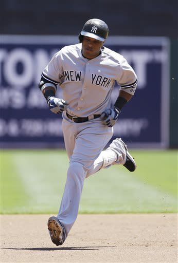 New York Yankees' Robinson Cano circles the bases after hitting a two-run homer off Oakland Athletics starting pitcher Jarrod Parker during the first inning of their baseball game Thursday, June 13, 2013 in Oakland, Calif. (AP Photo/Eric Risberg)