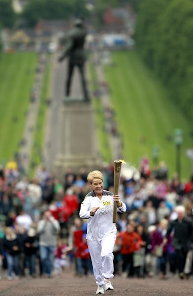 Geraldine McCann from Lurgan carries the Olympic torch at Parliament Buidings, Stormont, Belfast, Northern Ireland, Sunday, June 3, 2012. (AP Photo/Peter Morrison)