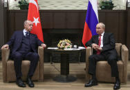 FILE - In this Sept. 29, 2021, file photo, Russian President Vladimir Putin, right, and Turkish President Recep Tayyip Erdogan talk to each other during their meeting in the Bocharov Ruchei residence in the Black Sea resort of Sochi, Russia. In Russia, it's common to get an antibody test for the coronavirus and share the results. Putin referred to his own test results while talking to Erdogan, bragging about how he avoided infection even though dozens of people around him caught the virus, including someone who spent a whole day with him. (Vladimir Smirnov/Sputnik, Kremlin/Pool Photo via AP)