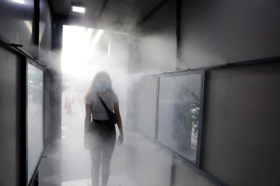 A woman wearing a mask passes through a sanitisation tunnel at a mall as India eases lockdown restrictions that were imposed to slow the spread of the coronavirus disease (COVID-19), in New Delhi, India, June 8, 2020. REUTERS/Anushree Fadnavis