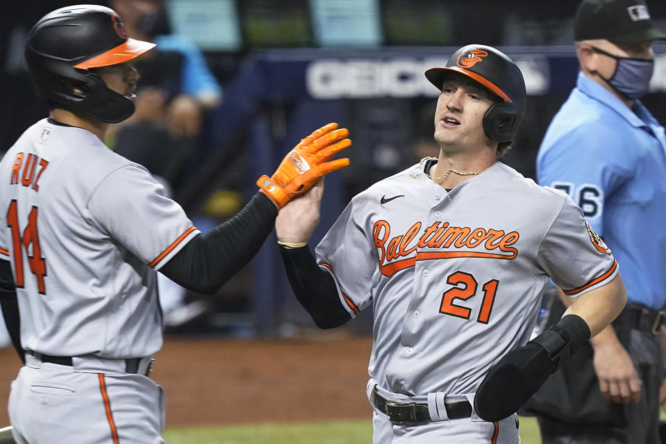 Baltimore Orioles' Rio Ruiz (14) congratulates Austin Hayes (21) after Hayes scores a run during the first inning of a baseball game against the Miami Marlins, Tuesday, April 20, 2021, in Miami. (AP Photo/Marta Lavandier)
