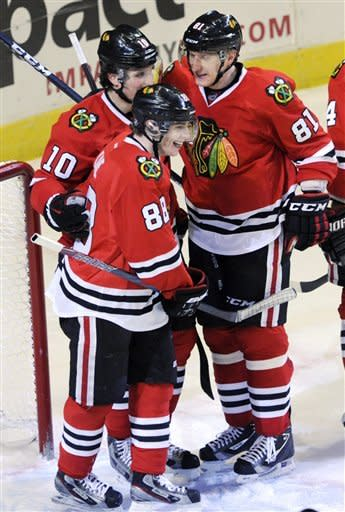 Chicago Blackhawks' Patrick Kane (88) celebrates with teammates Patrick Sharp (10), and Marian Hossa (81), of Slovakia, after scoring against the New York Rangers during the third period of an NHL hockey game in Chicago, Friday, March 9, 2012. Chicago won 4-3. (AP Photo/Paul Beaty)