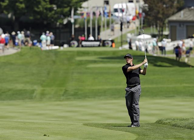 Rory McIlroy, from Northern Ireland, watches his approach shot to the 17th green during the first round of the Bridgestone Invitational golf tournament Thursday, July 31, 2014, at Firestone Country Club in Akron, Ohio. (AP Photo/Mark Duncan)